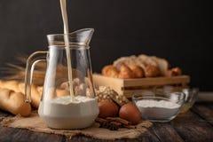 Vierta la leche en un jarro colocado en el saco imagen de archivo libre de regalías