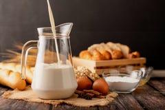 Vierta la leche en un jarro colocado en el saco fotografía de archivo