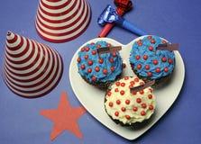 Viertes 4. der Juli-Parteifeier mit den roten, weißen und blauen Schokoladenkleinen kuchen und den Parteihüten Stockbilder