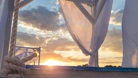 Vierte el toldo con las cortinas de la tela en la playa por la tarde foto de archivo libre de regalías