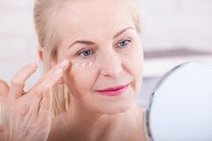 Vierzig Jahre alte Frau, die Falten im Spiegel betrachten Einspritzungen der plastischen Chirurgie und des Kollagens verfassung M Lizenzfreies Stockfoto