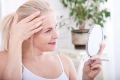 Vierzig Jahre alte Frau, die Falten im Spiegel betrachten Einspritzungen der plastischen Chirurgie und des Kollagens verfassung M Stockfotos