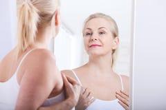 Vierzig Jahre alte Frau, die Falten im Spiegel betrachten Einspritzungen der plastischen Chirurgie und des Kollagens verfassung M Stockfotografie
