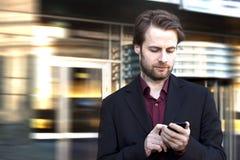 Geschäftsmann außerhalb des Bürohauses, das an einem Handy schaut Stockfotografie