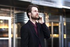 Geschäftsmann außerhalb des Büros sprechend an einem Handy Stockbild