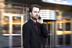 Geschäftsmann außerhalb des Büros sprechend an einem Handy Stockbilder