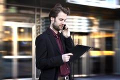 Geschäftsmann außerhalb des Büros sprechend an einem Handy Lizenzfreies Stockfoto