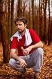 Läufermann, der einen Rest nach rüttelndem Training im Wald hat Stockfotos
