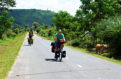 Traveller ride bicycle on the road conect Dalat to. Daklak, this is the nice road with fresh air, neglected landcape. Viet Nam- September 3, 2013 Stock Image
