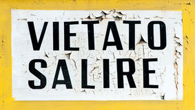 Vietato Salire Do Not Climb Sign. Old rusty and weathered Vietato Salire Italian Do Not Climb Sign in white and yellow Stock Photography
