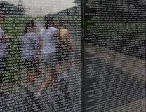Vietnam 1. The Vietnam War Memorial with jogging girls reflected in the background royalty free stock image