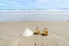 Vietnam Beach. Conical Hat or Traditional hat {Non La} and rattan or bamboo frame {to hold loads at the end of a carrying pole} in Danang beach, Vietnam Stock Photo