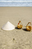 Vietnam Beach. Conical Hat or Traditional hat {Non La} and rattan or bamboo frame {to hold loads at the end of a carrying pole} in Danang beach, Vietnam Royalty Free Stock Photography