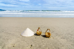 Vietnam Beach. Conical Hat or Traditional hat {Non La} and rattan or bamboo frame {to hold loads at the end of a carrying pole} in Danang beach, Vietnam Stock Image