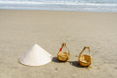Vietnam Beach. Conical Hat or Traditional hat {Non La} and rattan or bamboo frame {to hold loads at the end of a carrying pole} in Danang beach, Vietnam Royalty Free Stock Image