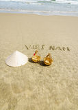 Vietnam Beach. Vietnam written on the sand. Conical Hat or Traditional hat {Non La} and rattan or bamboo frame {to hold loads at the end of a carrying pole} in Stock Image