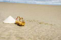 Vietnam Beach. Vietnam written on the sand. Conical Hat or Traditional hat {Non La} and rattan or bamboo frame {to hold loads at the end of a carrying pole} in Stock Photography