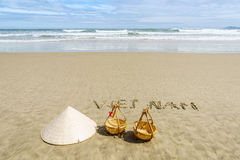 Vietnam Beach. Vietnam written on the sand. Conical Hat or Traditional hat {Non La} and rattan or bamboo frame {to hold loads at the end of a carrying pole} in Royalty Free Stock Photos