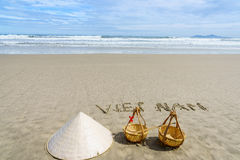 Vietnam Beach. Vietnam written on the sand. Conical Hat or Traditional hat {Non La} and rattan or bamboo frame {to hold loads at the end of a carrying pole} in Stock Photos