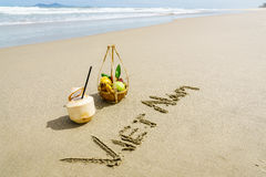 Vietnam Beach. Vietnam written on the sand with fruit basket and a coconut in Danang beach, Vietnam Royalty Free Stock Photos
