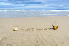 Vietnam Beach. Vietnam written on the sand with fruit basket and a coconut in Danang beach, Vietnam Royalty Free Stock Photo