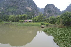 Tropical lake. A brown lake with impressing cliffs in the background in Vietnam royalty free stock photo