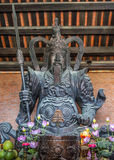 Vietnam Chua Bai Dinh Pagoda: Statue of fierce medieval warrior. Buddhist small altar in front of bronze bearded figure royalty free stock photos