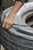 Vietnam - cutting rubber ribbon out of worn truck tire. Royalty Free Stock Image