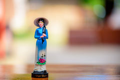 Vietnam doll souvenir on wooden table. With blurred background Stock Photo