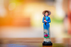 Vietnam doll souvenir on wooden table. With blurred background Stock Photos