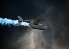 Vietnam era airplane flying through wall of smoke. Airshow performance by vintage Vietnam veteran airplane Cessna O-2A royalty free stock image