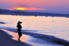 Vietnam fisherwoman. A Vietnamese fisherwoman working on beach at sunrise stock photo