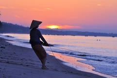 Vietnam fisherwoman. A Vietnamese fisherwoman working on beach at sunrise stock images