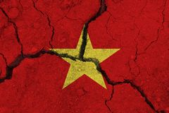 Vietnam flag on the cracked earth. National flag of Vietnam. Earthquake or drought concept stock photos