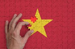 Vietnam flag is depicted on a puzzle, which the man`s hand completes to fold.  stock illustration