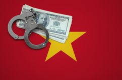 Vietnam flag with handcuffs and a bundle of dollars. The concept of breaking the law and thieves crimes.  royalty free stock photography