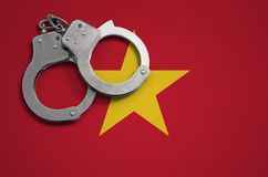 Vietnam flag and police handcuffs. The concept of crime and offenses in the country.  stock photo