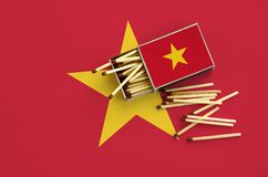 Vietnam flag is shown on an open matchbox, from which several matches fall and lies on a large flag.  royalty free stock photo