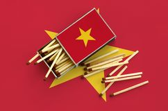 Vietnam flag is shown on an open matchbox, from which several matches fall and lies on a large flag.  royalty free stock image
