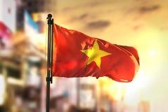 Vietnam flagga mot suddig bakgrund för stad på soluppgång Backligh Royaltyfri Bild