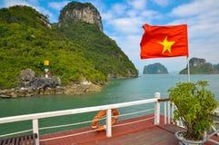 Vietnam flagga på bakgrunden av öarna av den Halong fjärden Arkivbilder