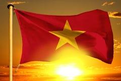 Vietnam flagga som väver på den härliga orange solnedgången med molnbakgrund Arkivbild