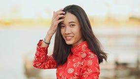 Vietnam flicka i den nationella röda klänningen Ao Dai som poserar och ler för kameran på sjösidan av Da Nang lager videofilmer