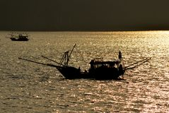 Vietnam - Ha Long Bay -evening light fishing boats in silhouette. Ha Long Bay AUCO cruise -evening light fishing boats in silhouette  - calm sea - - popular Royalty Free Stock Photo