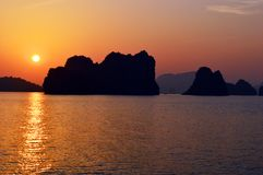 Vietnam - Ha Long Bay - limestone karsts silhouette at sunset closer up. Ha Long Bay AUCO cruise - limestone karsts silhouette at golden sunset panorama - calm stock image