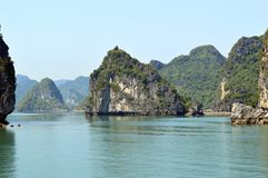 Vietnam - Ha Long Bay - small distinctive limestone karst in foreground with larger islands in the background. Ha Long Bay AUCO cruise -evening light small Royalty Free Stock Photos