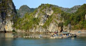 Vietnam - Ha Long Bay -small fish farm. Ha Long Bay - small fish farm with limestone karsts in the background - calm sea - colourful houses - popular travel Royalty Free Stock Photos