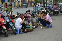 Vietnam - Hanoi - People sat on the side of the street eating lunch Royalty Free Stock Photography