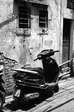 Vietnam - Hanoi -scooter parked against old decaying buildings in Hanoi - Typical street scene - black and white portrait. Vietnam - Hanoi - scooter parked Stock Photo