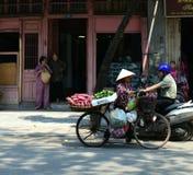 Vietnam - Hanoi - Typical street scene -ladies chatting in doorway whilst man on motorcycle and lady on pushbike go past. Vietnam - Hanoi - Typical street scene Stock Image